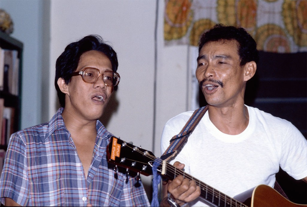 Taka with Ernie Alano, a teacher, playing the guitar in the Xavier faculty lounge, ~1975.